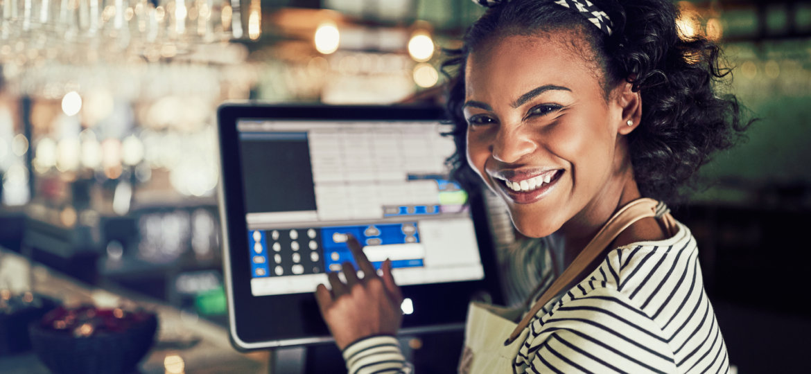 Smiling African waitress using a restaurant point of sale terminal